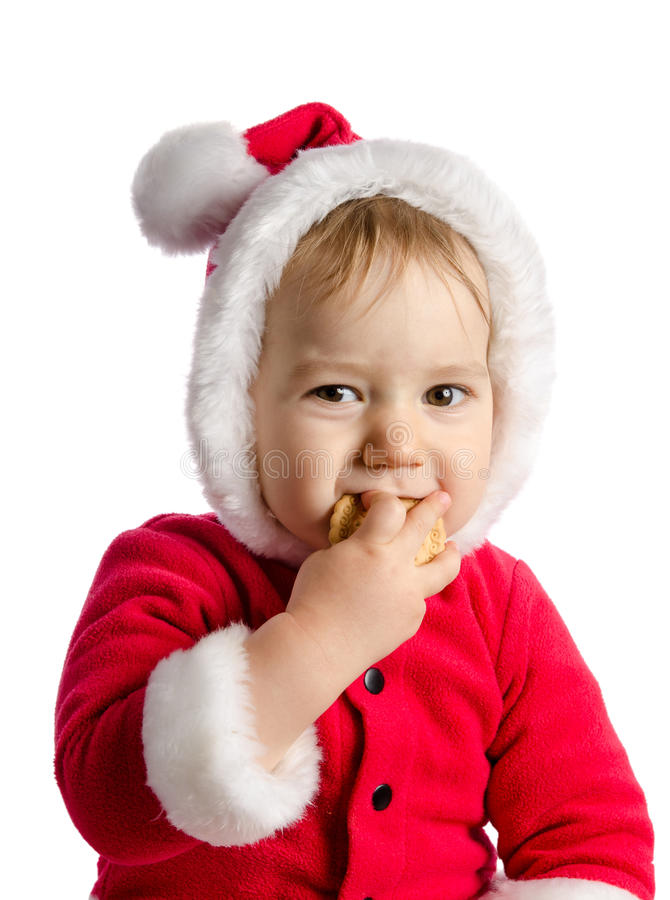 Funny baby in Santa Claus clothes eats cracker. On white background royalty free stock photos