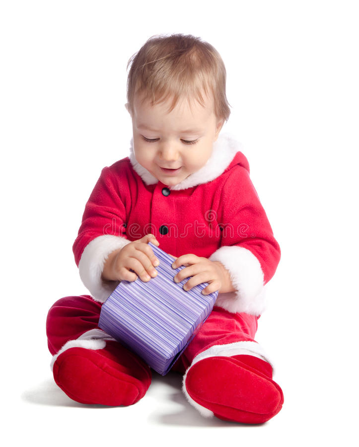 Funny baby in Santa Claus clothes with gift. Funny baby in Santa Claus clothes on white background with gift stock image