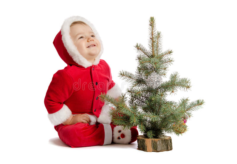 Funny baby in Santa Claus clothes with xmas tree. On white background stock photos