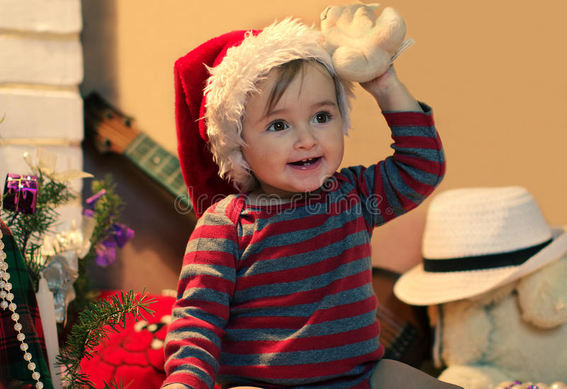 Funny baby in Santa hat with a stuffed teddy. Bear in her hand near christmas tree stock image