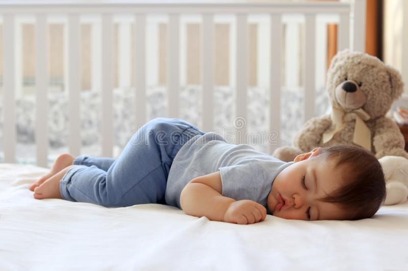 Little baby boy sleeping on stomach. Funny baby sleeping on his stomach on bed at home. Child daytime bottom up sleeping position stock image