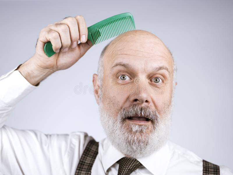 Funny bald man combing his head royalty free stock photos