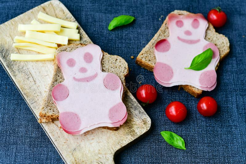 Funny bear face sandwich for kids. Healthy sandwich wits salami with bear face , basil, yellow cheese and cherry tomatoes royalty free stock photography