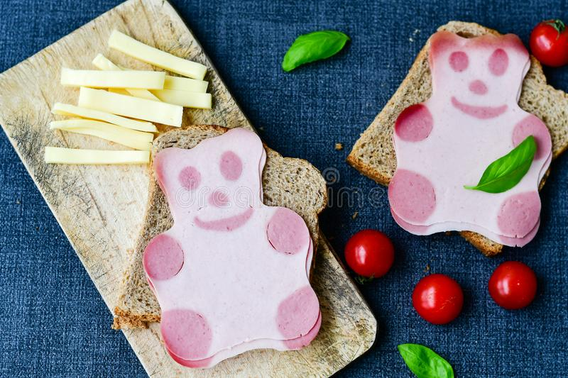 Funny bear face sandwich for kids. Healthy sandwich wits salami with bear face , basil, yellow cheese and cherry tomatoes royalty free stock image
