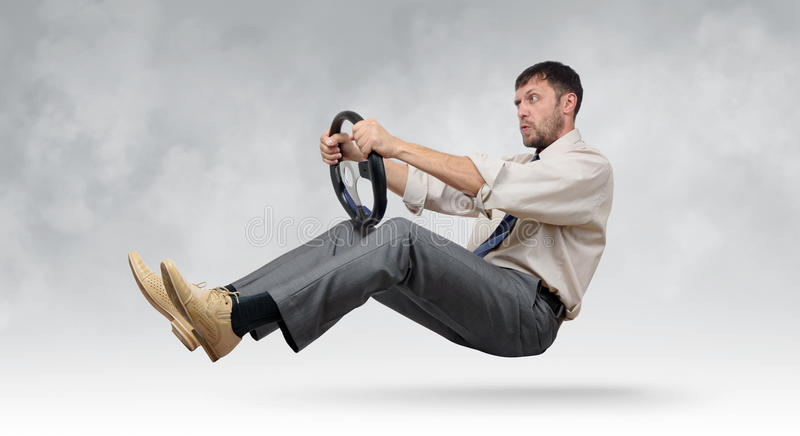 Funny bearded businessman with a steering wheel royalty free stock image