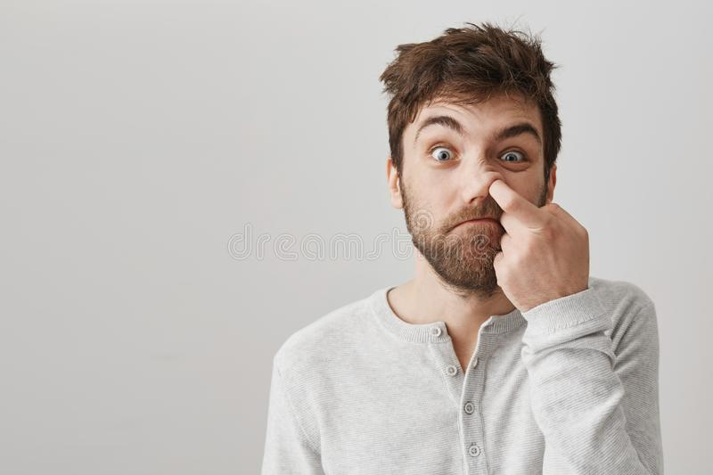 Funny bearded guy with messy hair and bad habits, staring at camera with stupid face, picking in nose with index finger. And standing over gray background stock image