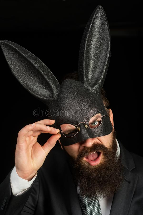 Funny bearded man in carnival rabbit mask. Bearded hipster in suit is ready for carnaval. Handsome man with beard in stock image
