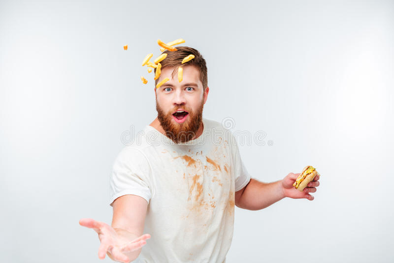 Funny bearded man in dirty shirt throwing french fries. On white background royalty free stock image