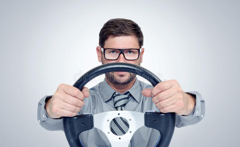 Funny bearded man in glasses with a steering wheel royalty free stock photo