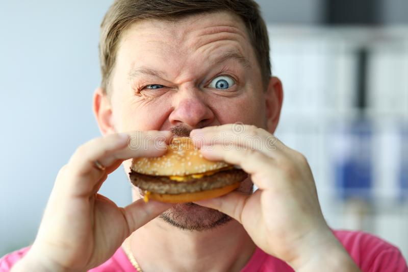 Funny bearded man with idiot facial expression eating big burger stock image