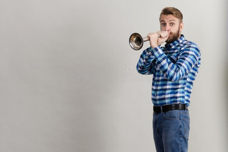 Funny bearded man in a plaid shirt blowing into the copper horn stock photo