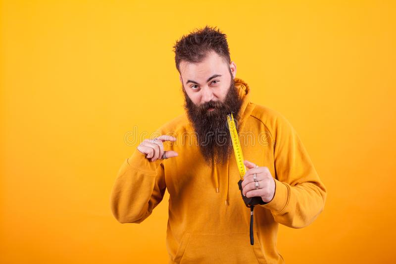 Funny bearded man showing dimension on roulette over yellow background. stock image