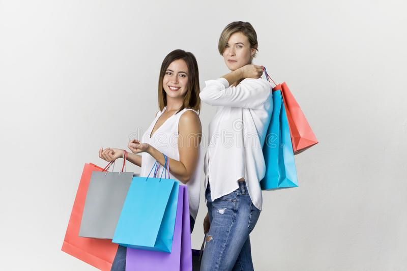 Funny beautiful attractive relaxed carefree girls with shopping stock photography
