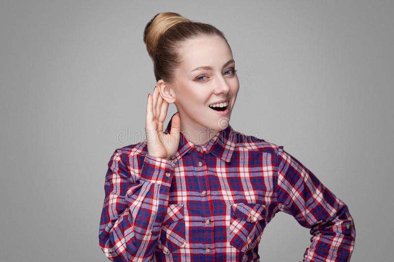 Funny beautiful blonde girl in red, pink checkered shirt, collected bun hairstyle, makeup standing and looking at camera with too. Thy smile and hearing. indoor royalty free stock photos