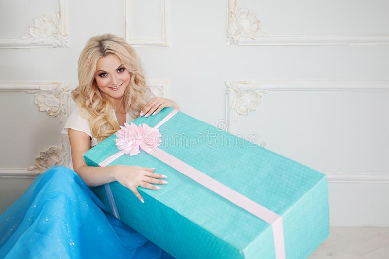 Funny and beautiful blonde with huge gift box. Charming young woman in a curvy blue skirt. royalty free stock photography
