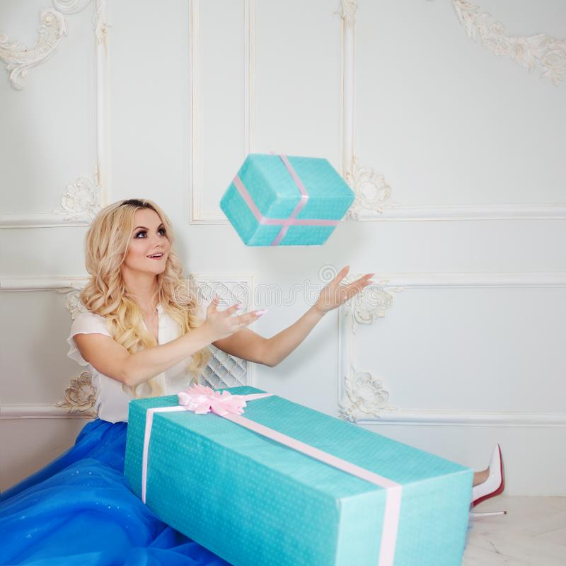 Funny and beautiful blonde with huge gift box. Charming young woman in a curvy blue skirt. royalty free stock photo
