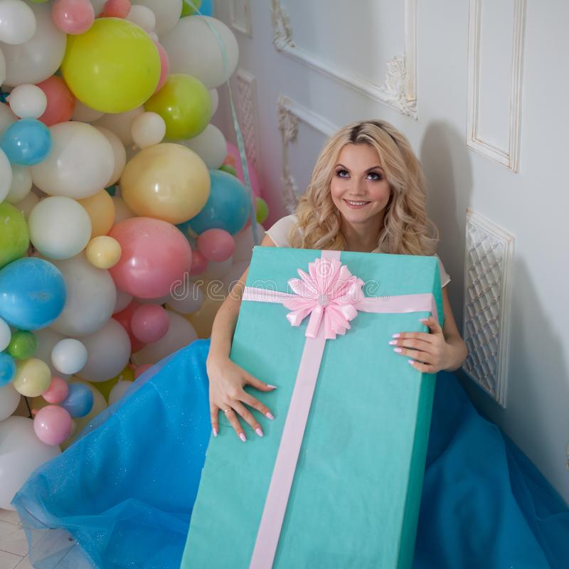 Funny and beautiful blonde with huge gift box. Charming young woman in a curvy blue skirt. stock photography
