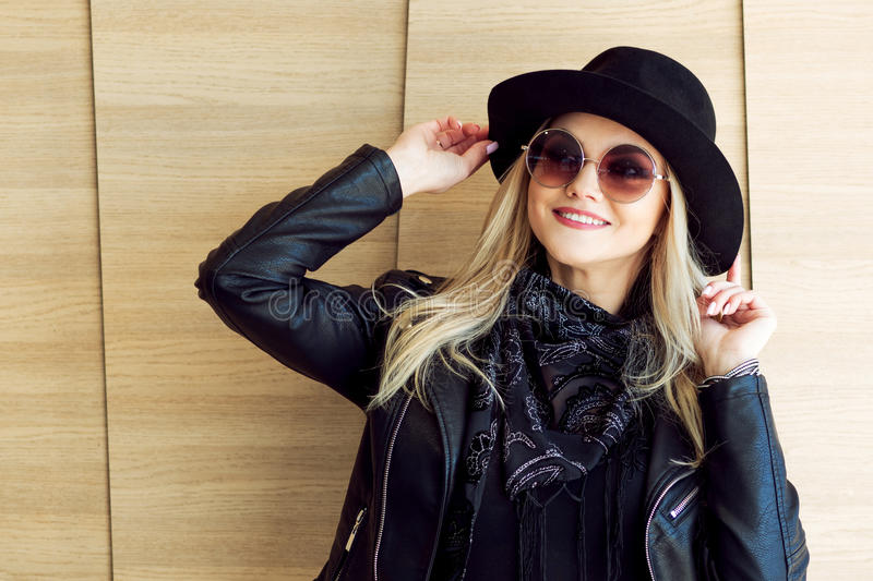 Funny and beautiful blonde in sun glasses and a hat. Trendy girl portrait outdoor. Laughs and holds hat. Toned picture royalty free stock image