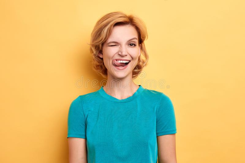 Funny beautiful positive woman sticking out her tongue at camera. As a sign of disobedience, protest and disrespect. Human emotions, facial expression .  yellow stock photos