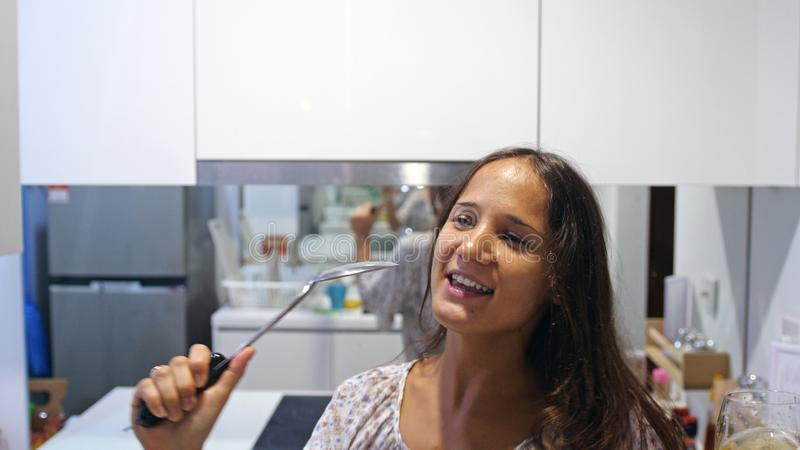Funny beautiful woman housewife in pajamas cookes dances and sings song with ladle while cooking in modern kitchen at royalty free stock image