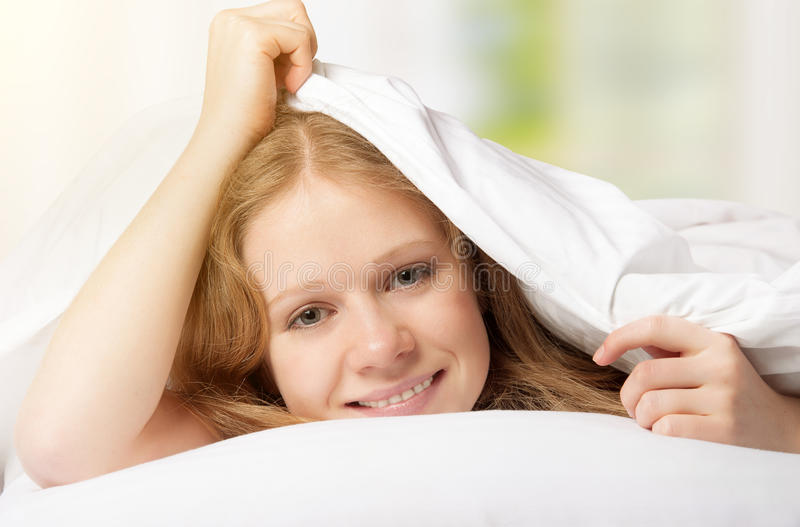 Funny beautiful woman under the blanket