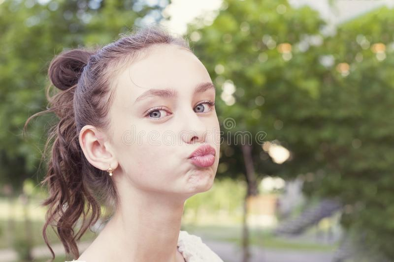 Girl keeps lips as going to kiss someone. Funny beautiful young girl keeps lips as going to kiss someone. Expresses his love to someone. Happy woman against park stock photography