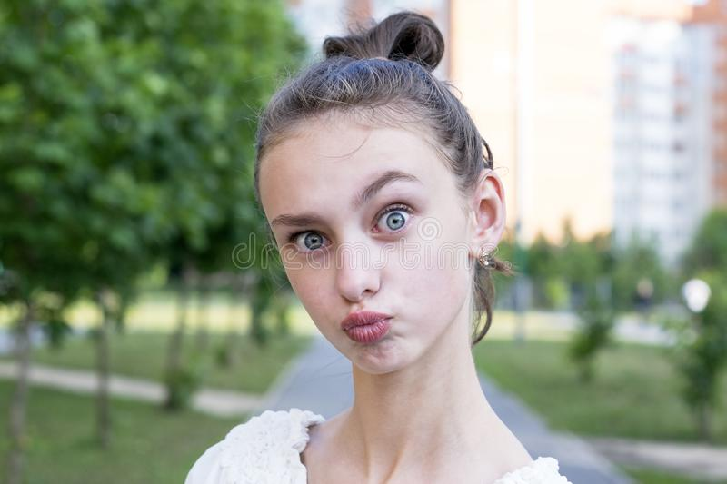 Girl keeps lips as going to kiss someone. Funny beautiful young girl keeps lips as going to kiss someone. Expresses his love to someone. Happy woman against park royalty free stock photos