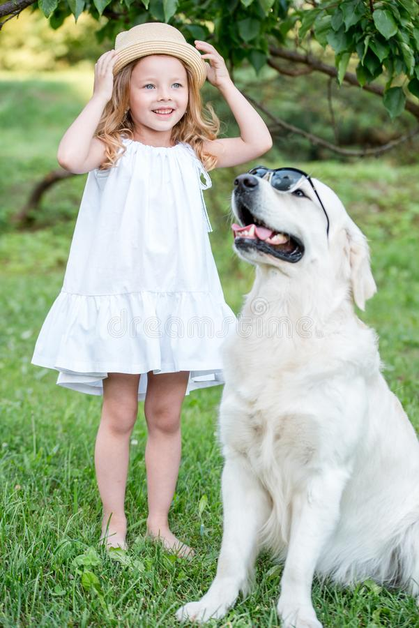 Funny big dog in sunglasses and cute blonde girl in white dress outdoors in park. royalty free stock photo