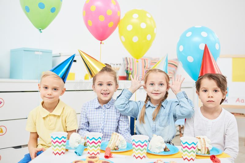 Funny birthday. Row of funny children in birthday caps sitting by festive table with pieces if cake, drinks and cookies royalty free stock photo