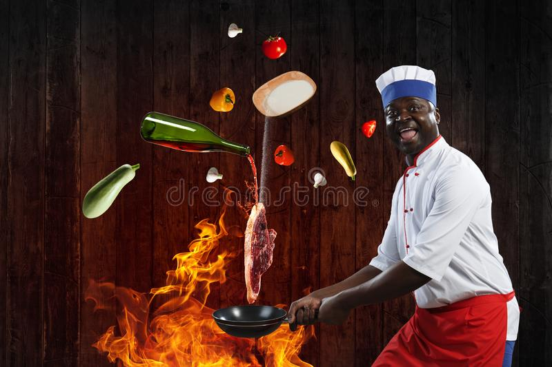 Black chef creative cooking. Mixed media. Funny black man in uniform, cookig steak on a frying pan, with ingredients around, wooden background royalty free stock photos