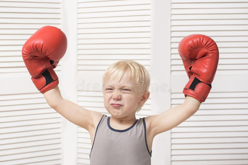 Funny blond boy in red boxing gloves. Sports concept.  royalty free stock image
