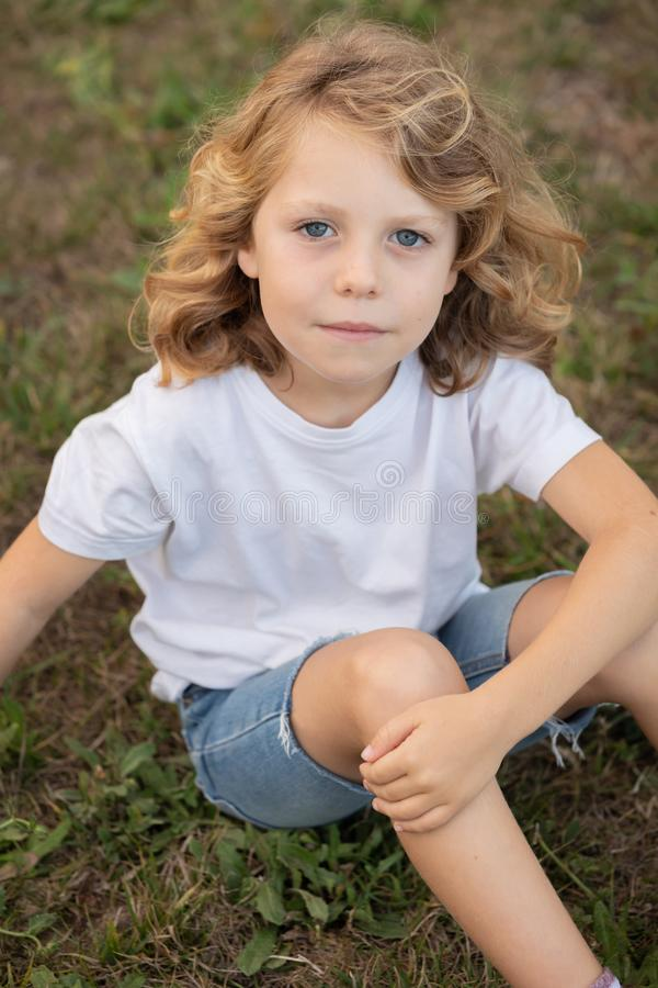 Funny blond kid with long hair stock image