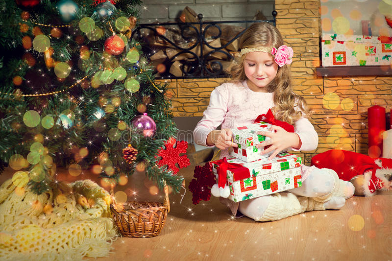 Funny blond toddler girl waiting for surprise from gift present royalty free stock images
