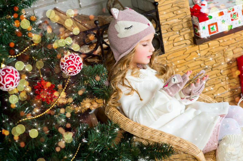 Funny blond toddler girl waiting for surprise from gift present royalty free stock photography