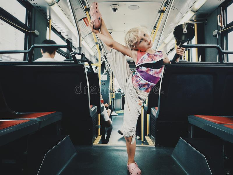 Funny blonde Caucasian girl riding on a bus and stretching stock image