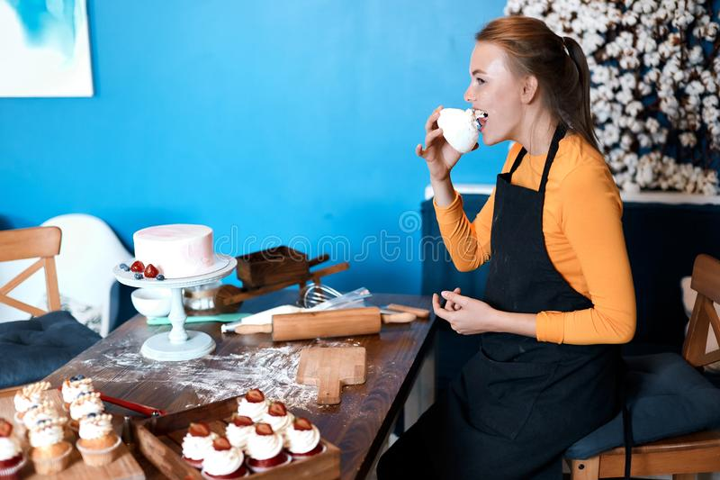 Funny blonde cook digustating cupcakes royalty free stock photo