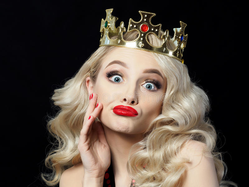 Funny blonde princess makes faces. Portrait of funny beautiful young blondie princess makes faces. Beautiful evening makeup. Model posing over black background royalty free stock image