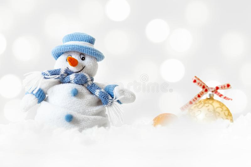 Funny blue snowman on xmas lights bokeh background, white snowflakes, merry Christmas and happy new year card concept. Happy funny snowman wearing blue hat and royalty free stock photo