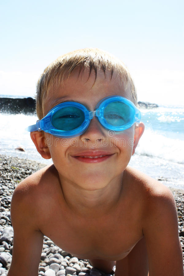 Funny boy. In sunglasses on the beach royalty free stock images