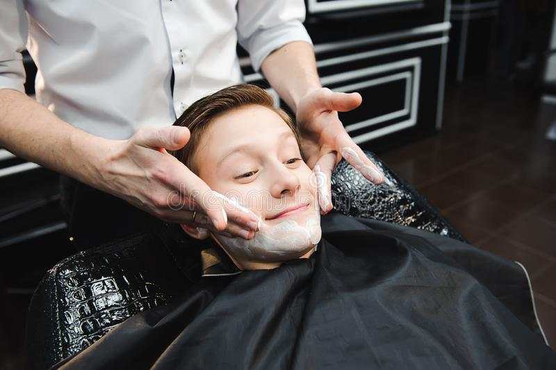 Funny boy in a black salon cape in the barbershop. Barber applies shaving foam with the help of the shaving brush on his. Face stock photos