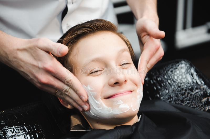 Funny boy in a black salon cape in the barbershop. Barber applies shaving foam with the help of the shaving brush on his. Face stock photography