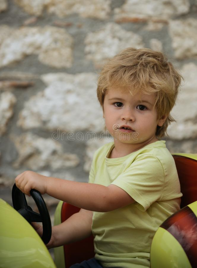 Funny boy car driver with steering wheel. Cute boy in yellow T-shirt in red toy car. Little boy driving big toy car and royalty free stock images