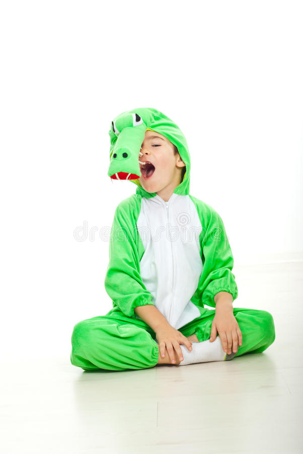 Funny boy in crocodile oufit. Funny boy dressed in crocodile outfit sitting on floor with legs crossed and big mouth open.Check also stock image