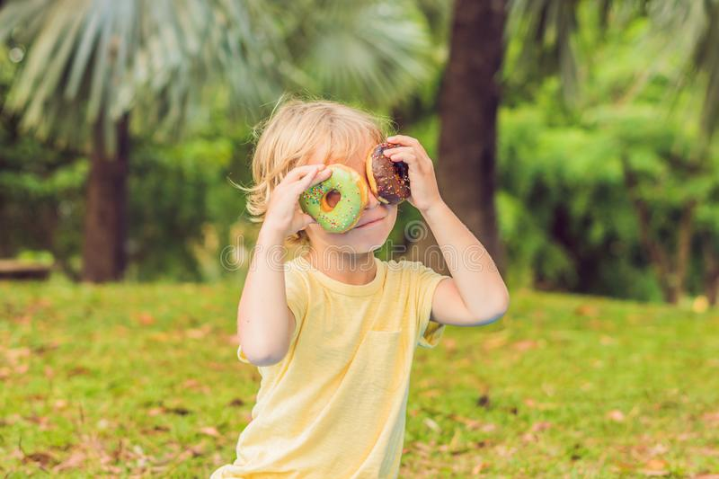 Funny boy with donut. child is having fun with doughnut. Tasty food for kids. Happy time outdoor with sweet food stock photo