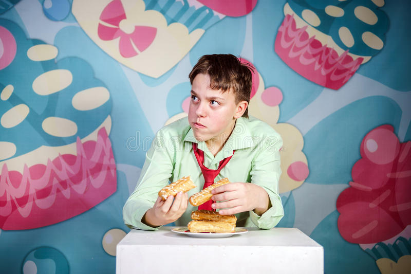 Funny boy eating sweet cakes, hungry and candy man. Funny teenage boy eating sweet cakes, hungry and candy man royalty free stock photo