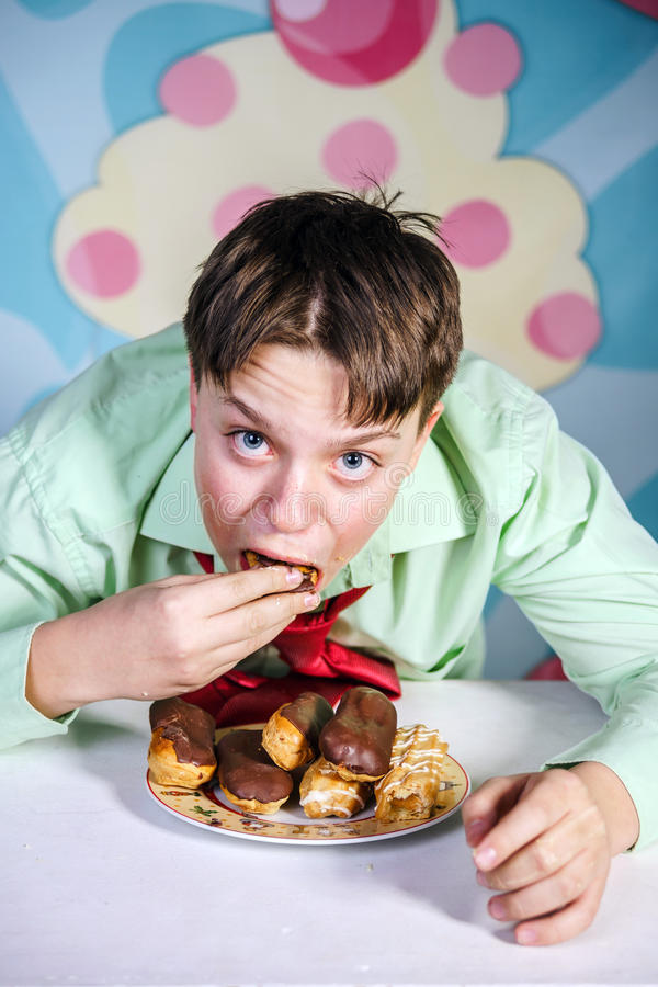 Funny boy eating sweet cakes, hungry and candy man. Funny teenage boy eating sweet cakes, hungry and candy man stock photo