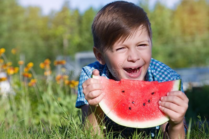 Funny boy eats watermelon outdoors in summer park royalty free stock image