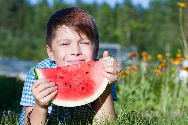 Funny boy eats watermelon outdoors in summer park stock photo
