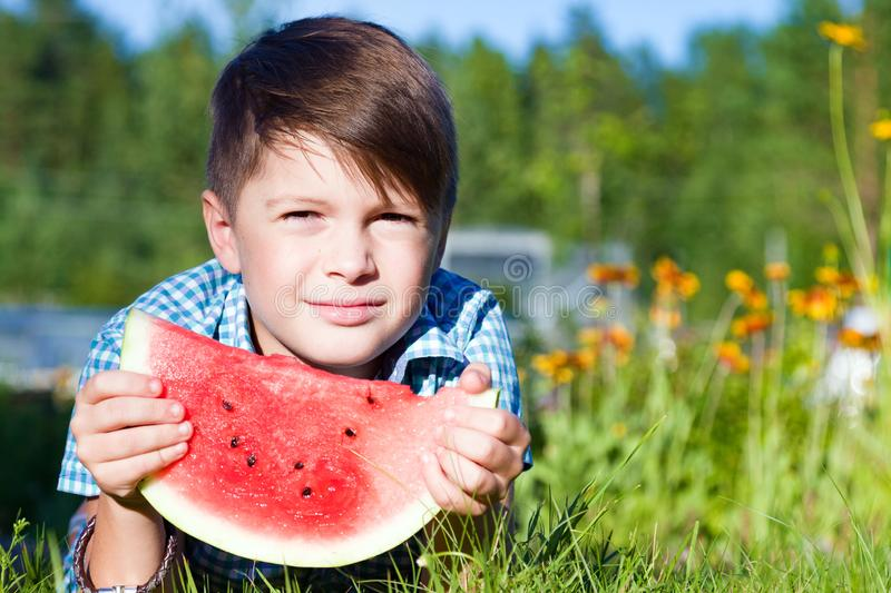 Funny boy eats watermelon outdoors in summer park stock images