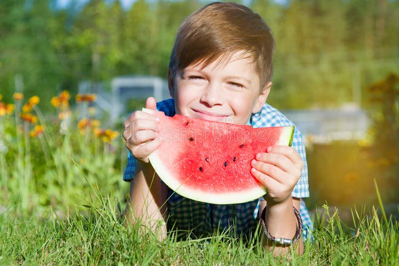 Funny boy eats watermelon outdoors in summer park royalty free stock images